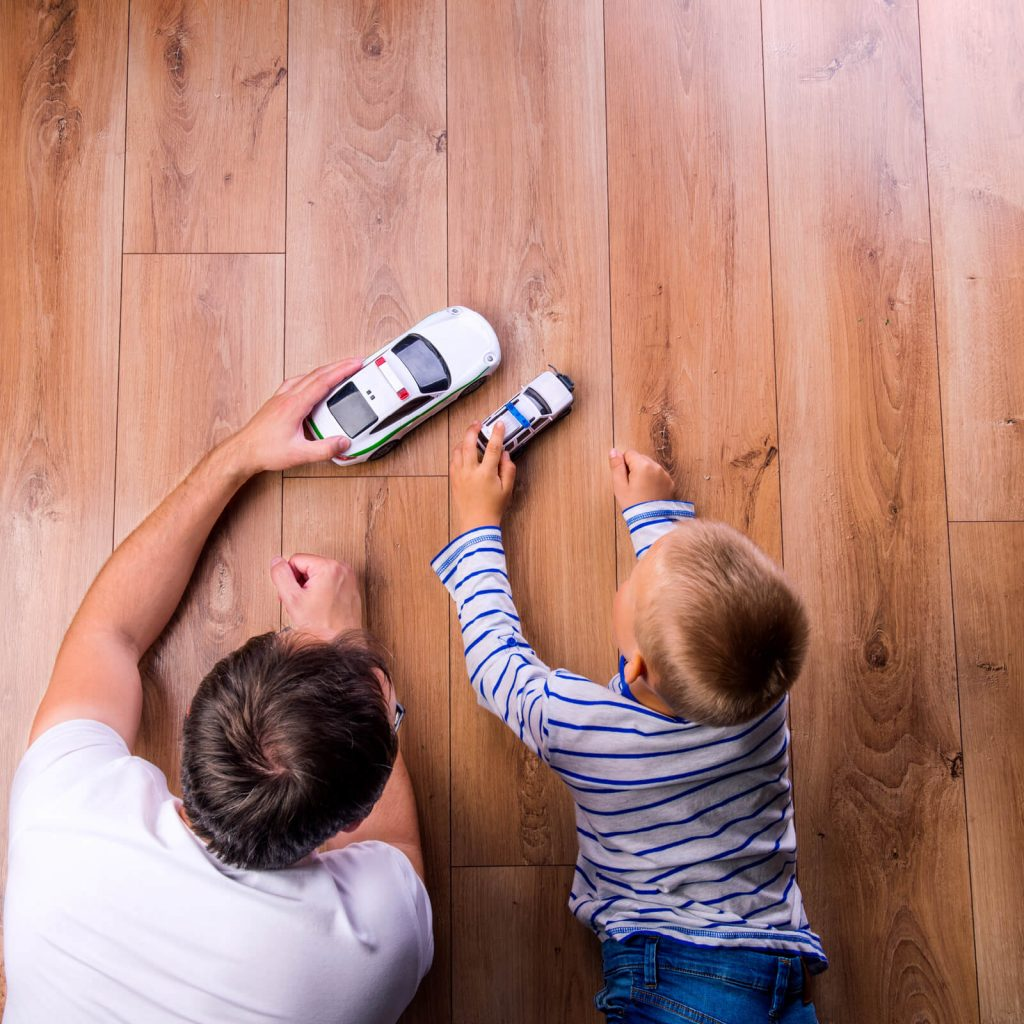 Father with kid playing with toycar | Tom January Floors